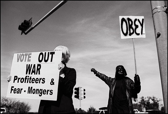 A peace activist in Santa Fe dressed as Darth Vader stands behind a woman who is holding a sign that says Vote out war profiteers and fear-mongers.