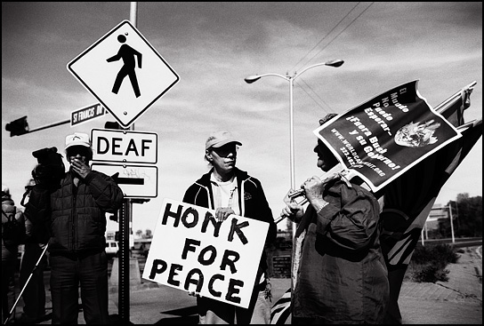 A group of peace activists in Santa Fe holding signs that say Honk for peace.