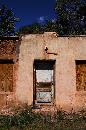 The front door of an abandoned adobe house in Pecos, New Mexico. The plaster and adobe are falling away from the front of the ruined building.