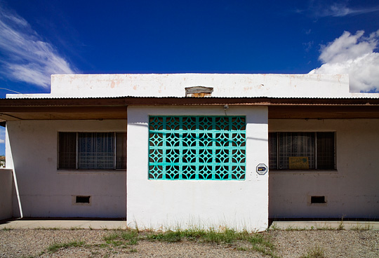 An abandoned cantina bar in Pecos, New Mexico. The building is a white cinderblock building with decorative concrete bricks in the entrance.