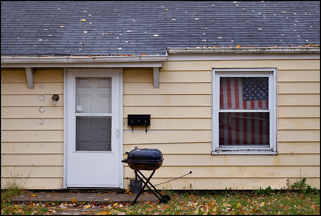 A charcoal grill in front of a small yellow house with an American flag used as a curtain on one of the windows.