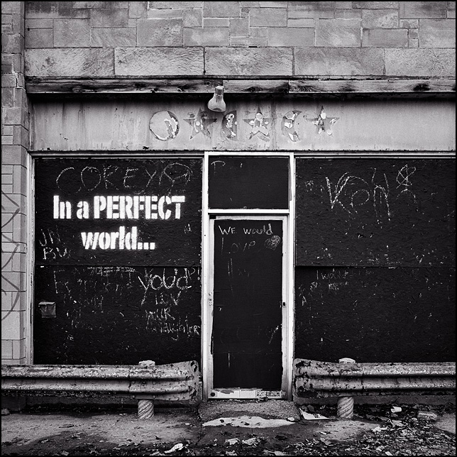 A boarded up storefront on College Avenue in the inner-city of Indianapolis that has the phrase In a 'PERFECT World' painted on it. Chalk is provided for people to write their ideas. In a perfect world we would love our neighbors.