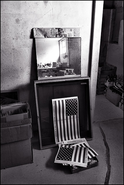 Newsprint American flags that came in the newspaper are piled up on a stack of old papers in my grandmothers basement.