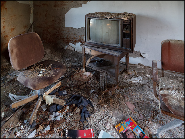 An old television set, porn magazines, and XXX movies in the living room of an abandoned farmhouse in rural Allen County, Indiana. Broken plaster covers the floor and the chairs in the room.
