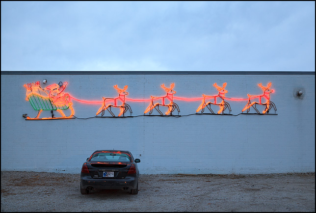 Huge lighted Santa and sleigh with reindeer on the side of a cinderblock building, Peters Body Shop on Bluffton Road in Fort Wayne, Indiana.