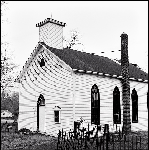 The little white church and wrought iron fence at the Prairie Grove Cemetery in the Waynedale area of Fort Wayne, Indiana. The chapel is white clapboard with black arched windows and a brick chimney.