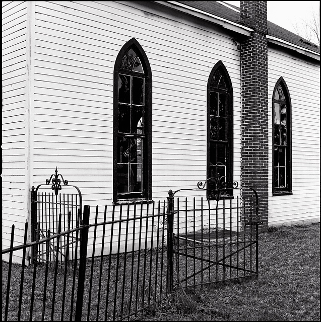 An old white church with pointed arch windows behind the wrought iron fence around the Prairie Grove Cemetery in the Waynedale section of Fort Wayne, Indiana.