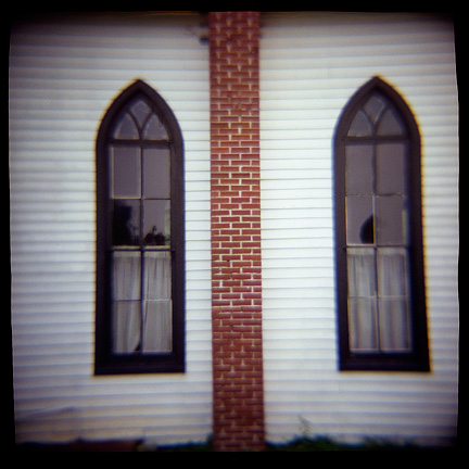 Pointed windows and brick chimney on the old white church in the Prairie Grove Cemetery in Waynedale, photographed with a Diana toy camera.