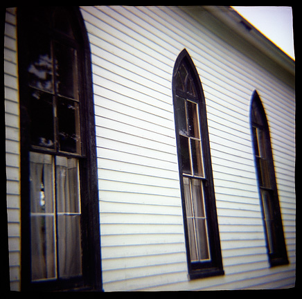 Pointed windows of the old white church in the Prairie Grove Cemetery in Waynedale, photographed with a Diana toy camera.