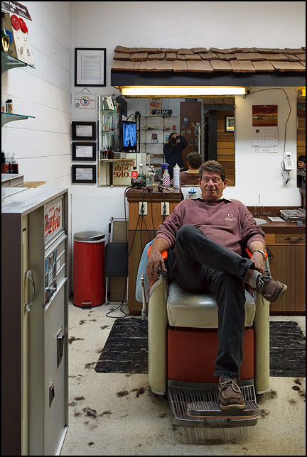 Phil Luginbill in his chair at Time Corners Barber Shop in Fort Wayne, Indiana. An old Coca-Cola machine sits along the wall in front of him.