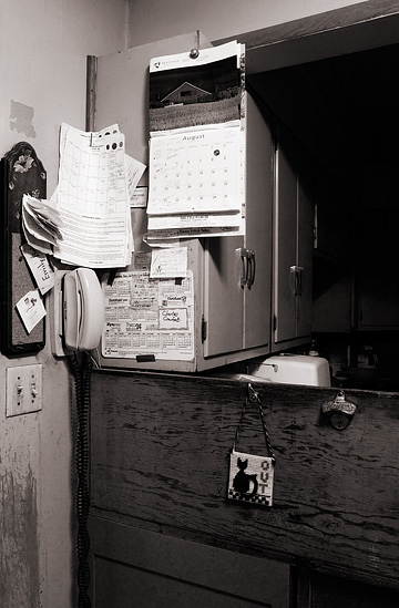The area around the phone in my grandfather's kitchen. The bulletin board is covered in notes and several calenders hang on the wall while an old Pepsi bottle opener hangs on the wall nearby.