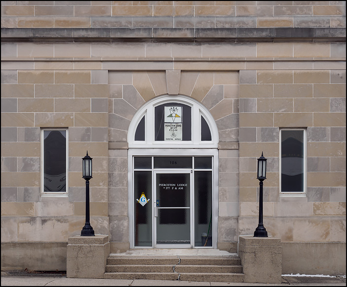 Freemasons Lodge 377 in the small town of Pierceton, Indiana. The front door of the limestone building is flanked by old-fashioned lights.