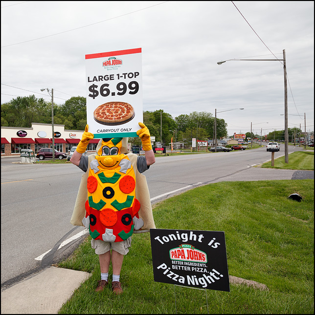 A man wearing a Pizza Slice costume while holding a Papa Johns sign on Bluffton Road in the Waynedale area of Fort Wayne, Indiana.