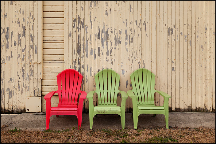 Three plastic Adirondack chairs, a red chair and two green chairs, sit in front of an old yellow garage door with peeling paint in rural Allen County, Indiana.