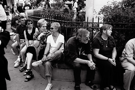 Middle aged tourists sitting in front of the wrought iron fence that surrounds the war monument on the Santa Fe Plaza.