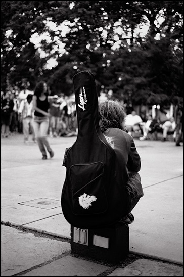 A musician with his guitar case strapped to his back watching people dance during a concert on the Santa Fe Plaza.