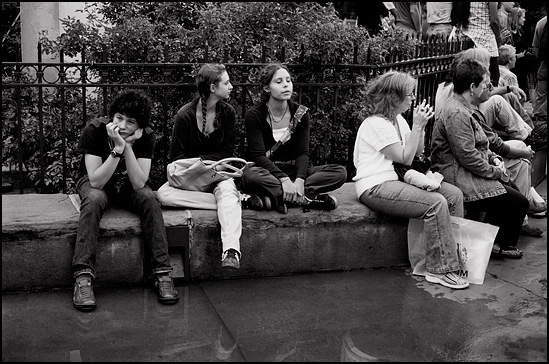 A group of bored teens sitting on the wall around the monument on the Santa Fe Plaza.