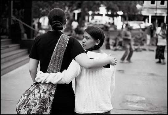 A girl and her younger sister stand with their arms around each other while they watch people dance during an evening concert on the Santa Fe Plaza.