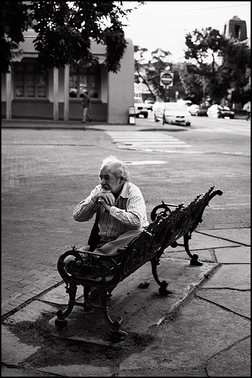 An elderly Asian man sits deep in thought on a park bench with his chin rested on his cane during a concert on the Santa Fe Plaza.