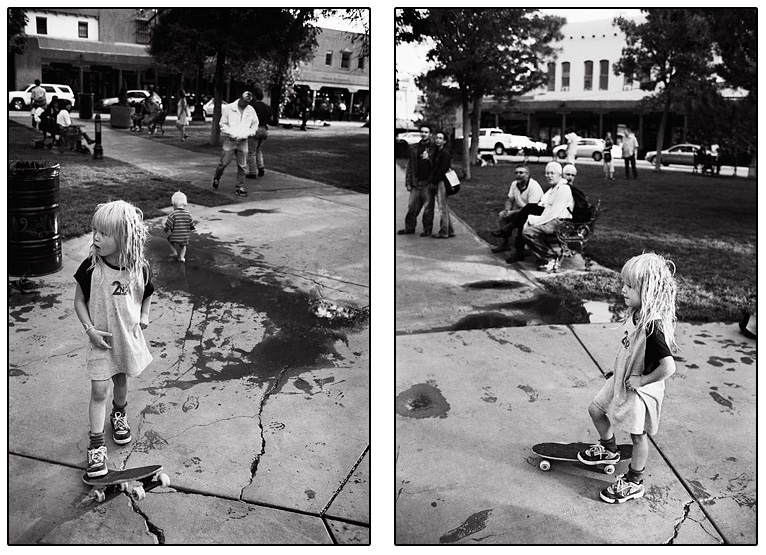 A little blond girl with dreadlocked hair stands with her hand on her hip and her foot on her skateboard on the plaza in downtown Santa Fe, New Mexico.