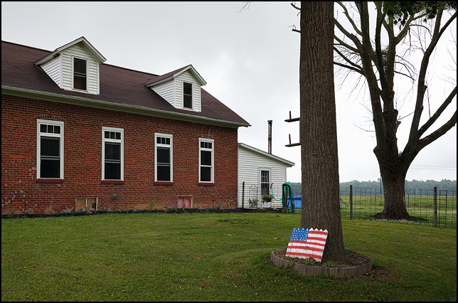A hand-painted American flag on a piece of wood picket fence leaned against a tree next to a US Army veteran's brick house on Pleasant Center Road in rural Allen County, Indiana. The house is a former one-room schoolhouse built in the 1850s.