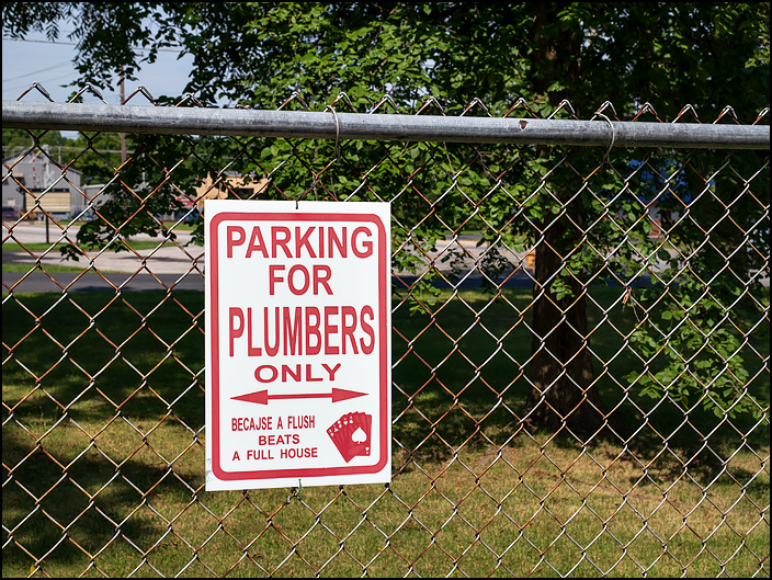 A sign on the fence behind Waynedale Plumbing Supply. Parking For Plumbers Only, because a flush beats a full house.