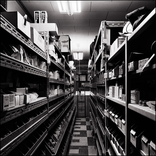 A narrow aisle lined with floor to ceiling shelves and bins full of small parts and plumbing fixtures in an old locally owned shop in the Waynedale area of Fort Wayne, Indiana.