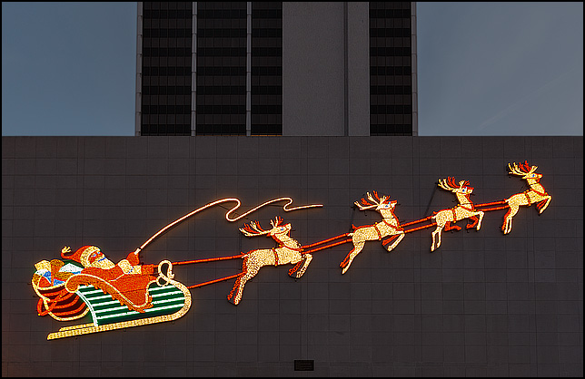 The historic Wolf and Dessauer Santa and Reindeer display lit up on the side of the PNC Bank Building on Main Street in downtown Fort Wayne, Indiana.
