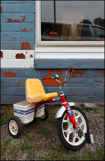 A red childrens tricycle with a yellow sear sits in front of an auto repair garage at the corner of Winchester Road and Yoder Road in the small town of Poe, Indiana.