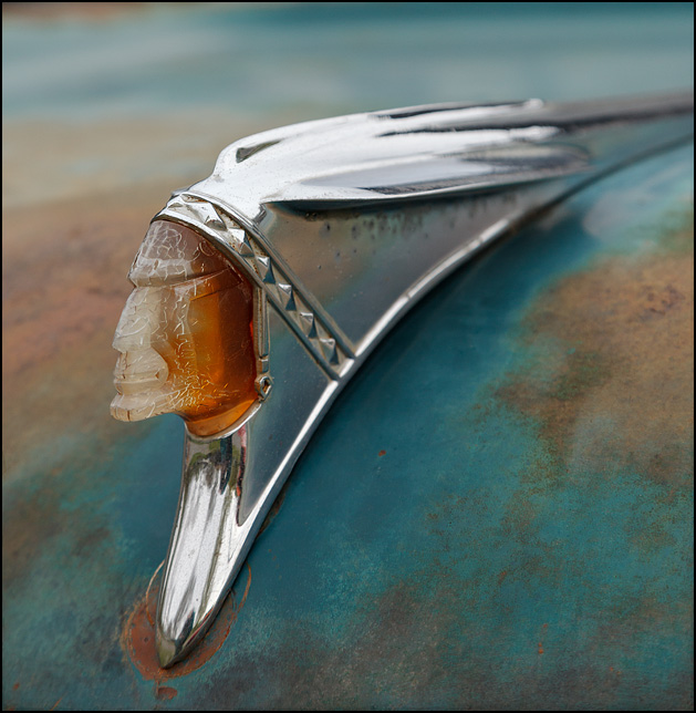 A 1958 Pontiac Indian Head Hood Ornament mounted on a turquoise Chevrolet Viking truck.