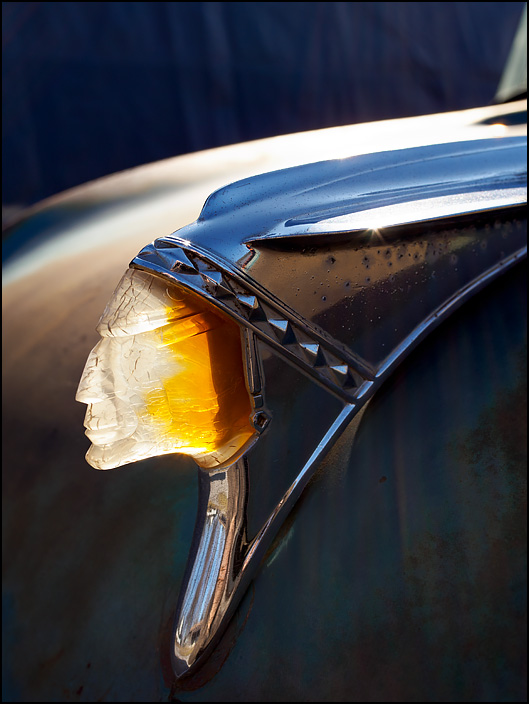 A 1958 Pontiac Indian Head Hood Ornament glows with light as the bright sun streams through it from behind.