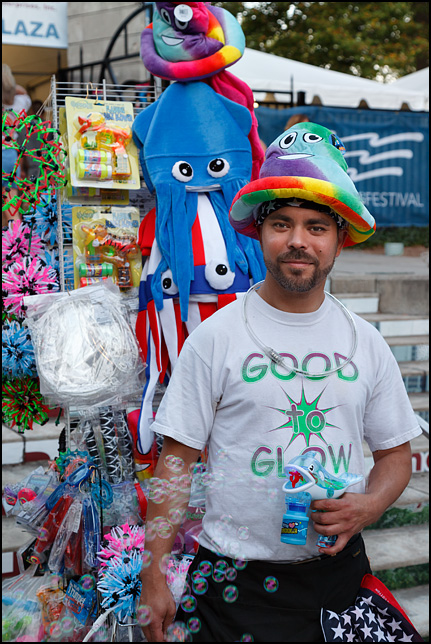 A man selling novelty hats and toys is wearing a rainbow-colored Poop Emoji hat and shooting bubbles from a bubble gun at the Three Rivers Festival in Fort Wayne, Indiana.