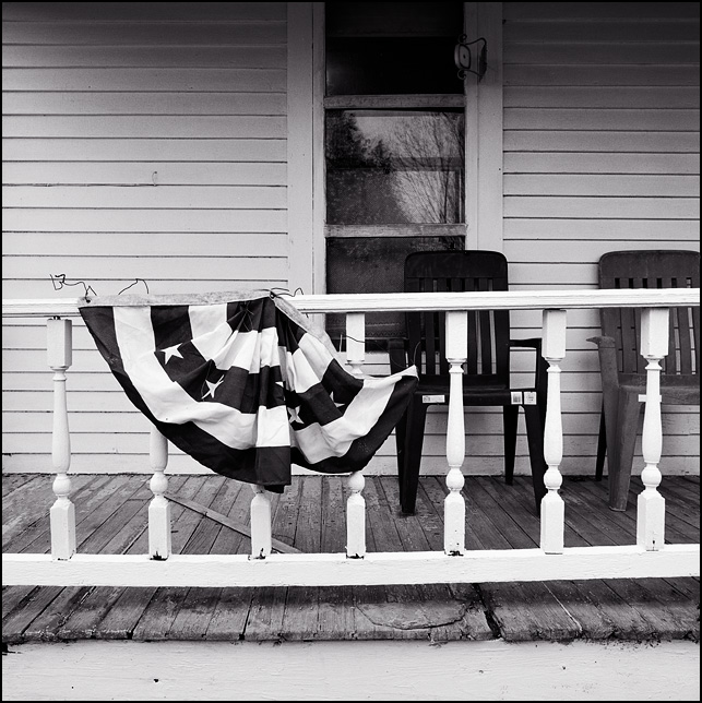 Plastic patio chairs and patriotic bunting on the front porch of an abandoned farmhouse on Pleasant Center Road in Allen County, Indiana.
