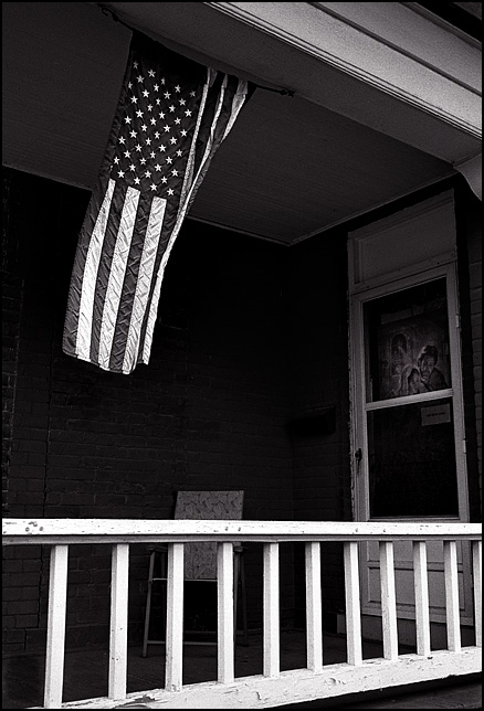 An American flag blows in the wind over the front porch of an old brick house at the corner of Maumee Avenue and Sidney Street in Fort Wayne, Indiana. A chair sits on the porch behind the rail under the stars and stripes.