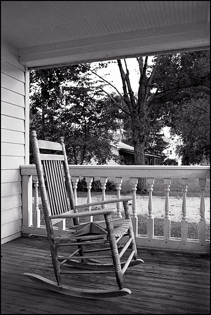 A wooden rocking chair on the front porch of a house in Indiana.