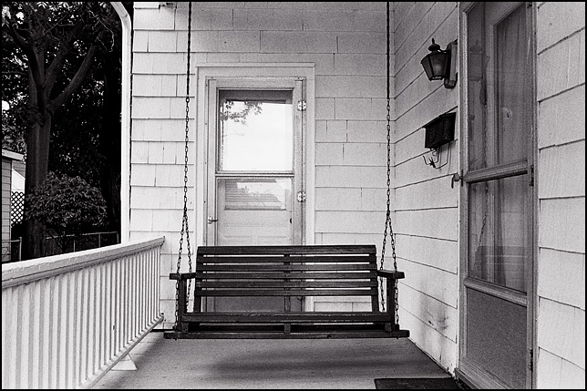 An old wooden porch swing hangs in front of the door of a house on Wells Street in Fort Wayne, Indiana.