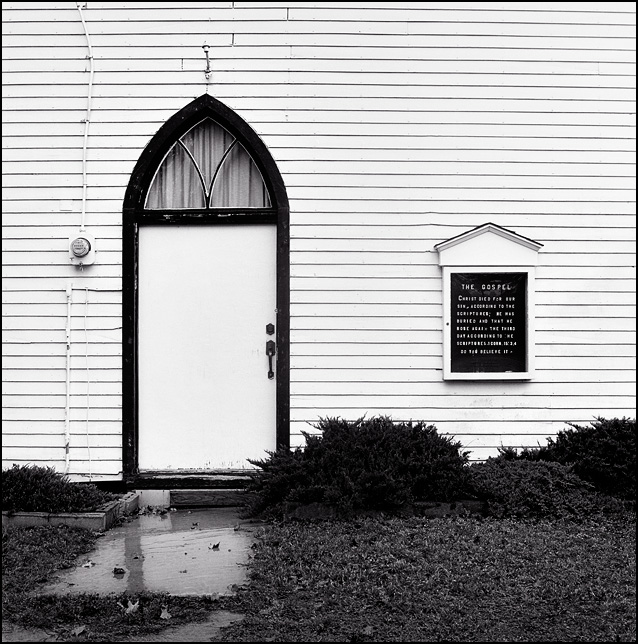 The front door and sign on the old chapel at Prairie Grove Cemetery in the Waynedale area of Fort Wayne, Indiana. The sign asks if you believe in the Gospel.