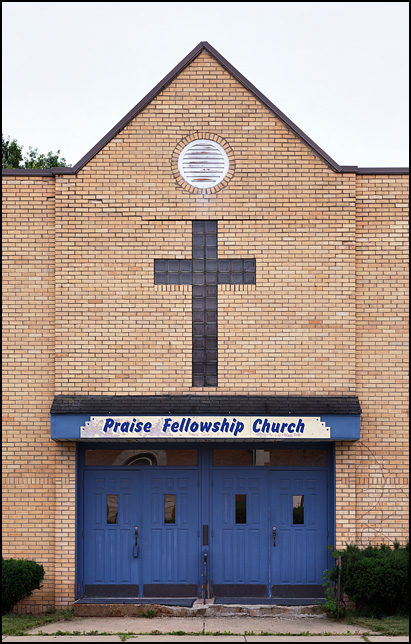 Praise Fellowship Church on Third Street in Mishawaka, Indiana; a yellow brick church with a glass brick cross over the front entrance.