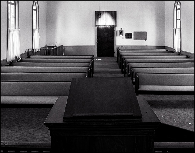 A view from the pulpit looking out over the old wooden pews in the little white wooden church in the Prairie Grove Cemetery in the Waynedale area of Fort Wayne, Indiana. The chapel has pointed arch windows and a single small door in the back of the church. Lacy curtains cover all of the windows.