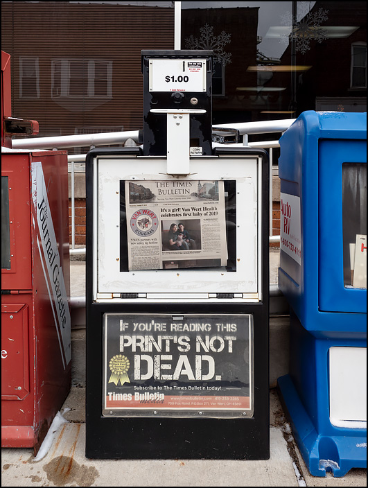 A newspaper machine selling the Van Wert Times Bulletin in the small town of Convoy, Ohio. The sign on the machine says, If you can read this print is not dead.