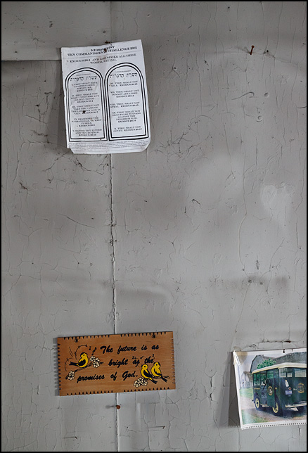 A piece of paper with the Ten Commandments nailed to the wall in an abandoned house above a wooden sign that says, The future is as bright as the promises of God.