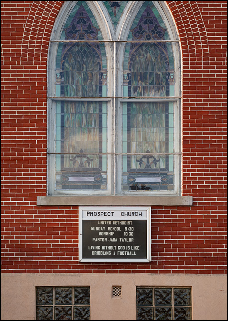 Living Without God is Like Dribbling a Football, the sign under the stained glass windows on the front of Prospect United Methodist Church in rural Wells County, Indiana.