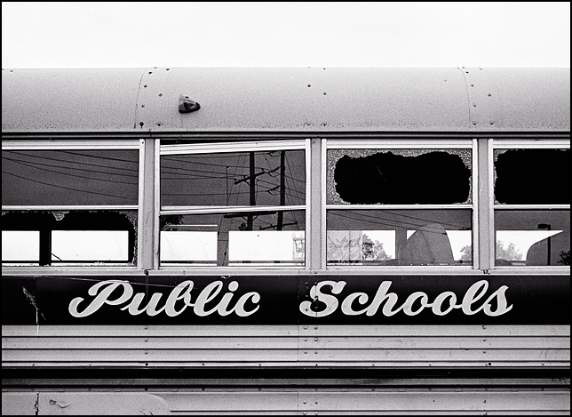 An old school bus with broken windows that has Public Schools painted on the side instead of the name of the school district.