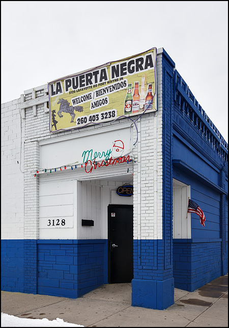 A small American flag and a Merry Christmas sign hang by the door of La Puerta Negra, a Hispanic bar in Fort Wayne, Indiana.