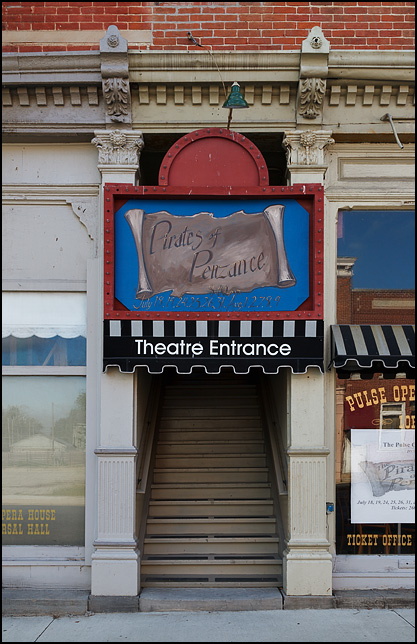 Entrance to the Pulse Opera House in the small town of Warren, Indiana. The handpainted sign over the door advertises upcoming performances of The Pirates of Penzance.