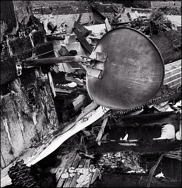 A satellite TV dish still hangs from a charred wall in the pile of ashes from a farmhouse that burned down in front of the abandoned Pure Sealed Dairy in Fort Wayne, Indiana.