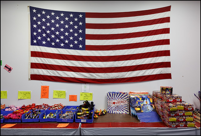 A large American flag hangs on the wall above a table stocked with fireworks and patriotic signs at the Pyromaniac Fireworks store in Fort Wayne, Indiana.
