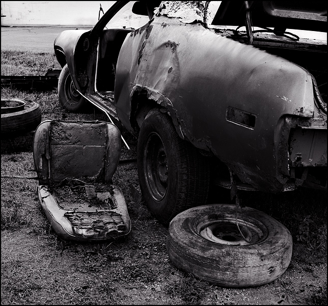 An abandoned car stripped of its interior and engine. The front seat and some old tires are on the ground next to the car.