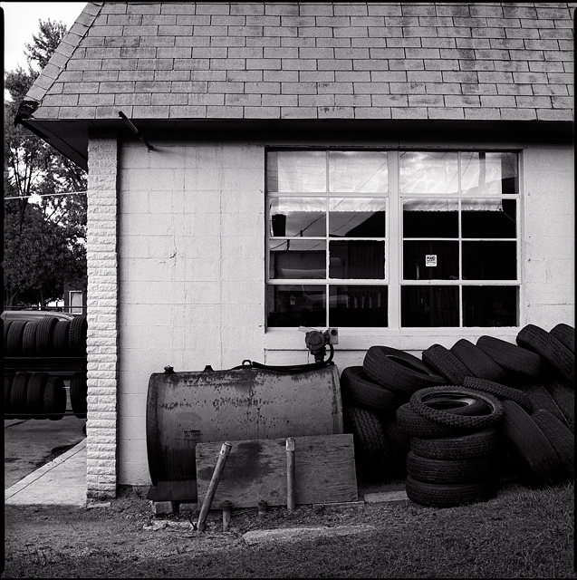 Used tires piled up next to an old rusty oil tank at Quest Tire and Auto on Lower Huntington Road in the Waynedale area of Fort Wayne, Indiana.
