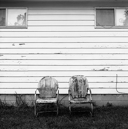 Two old rusty metal motel chairs sit under the windows on the front of my grandfather's old house in the rain.